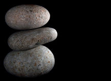 Balancing Rocks. Rough river rocks balancing with a black background Royalty Free Stock Image
