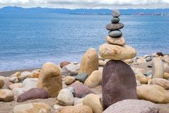 Balancing Rocks. Rocks stacked one one top of another on beach in Puerto Vallarta,  Banderas bay in background. This is an art form of Zen. Space on left for Royalty Free Stock Photos