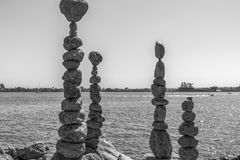 Balancing Rocks in black and white. Different size of rocks balanced on top with view of water royalty free stock images