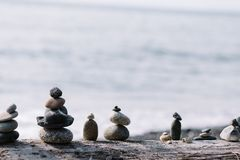 Balancing rocks on each other at the beach stock photography