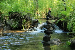 Balancing rocks tower with coffe cup. Balancing rocks tower in river stock photography