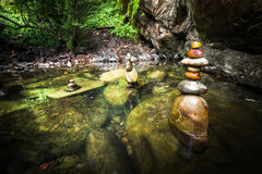 Balancing rocks tower for zen meditation practice. Amazing tropical rain forest landscape with lake and balancing rocks tower for zen meditation practice. Nature Royalty Free Stock Image