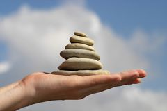 Balancing stones. Pile of stones on the hand, sky and clouds background Royalty Free Stock Images