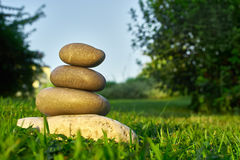 Balancing stones on the grass Stock Image