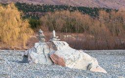 Balancing stones on a lake shore Royalty Free Stock Photography