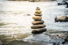 Balancing stones on river rocks. Balancing stones on a river rocks. Stability concept in a turbulence world stock images