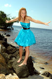 Balancing teen on rocks. A teen in her prom dress balancing on the rocks at the beach royalty free stock photos