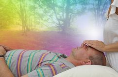 Balancing Third Eye Chakra. Healing practitioner sensing energy of male client lying supine on couch with rainbow colored fantasy woodland scene in background Royalty Free Stock Photography