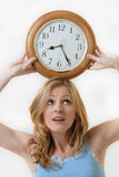Balancing time. Attractive blond woman holding a round clock balanced on head at the time eight twenty-five showing time management Royalty Free Stock Photos