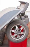 Balancing a wheel in the workshop. A wheel balancing tool in a workshop in the process of balancing a wheel Stock Photos