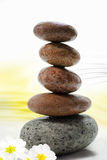 Balancing zen stones. Pile of balancing smooth zen stones with flowers on decorative white background Royalty Free Stock Image