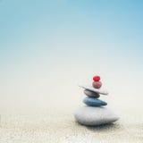 Balancing zen stones pyramid on sand Royalty Free Stock Photo