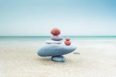 Balancing zen stones pyramid on sand. Balancing colorful zen stones pyramid on sandy beach under blue sky. Beautiful nature and spiritual concept Stock Photo