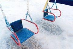 Balanço coberto de neve e corrediça no campo de jogos dentro Fotografia de Stock