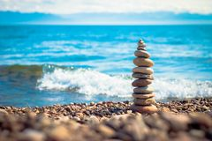 Balansera stenar på bakgrunden av den annalkande vågen Royaltyfria Bilder