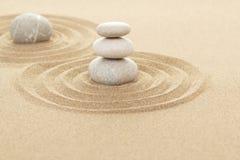 Balansera zenstenar i sand Arkivbild