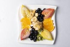 Balanserad exotisk fruktsallad p? plattan, riktig n?ring arkivbild
