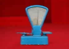 Balanza azul llevada vieja en fondo rojo Imagenes de archivo