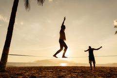 Balanza de los adolescentes en silueta del slackline Imagen de archivo libre de regalías