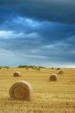 Balas de feno no campo com céu tormentoso Imagens de Stock
