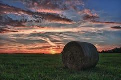 Balas de heno en un prado contra el cielo hermoso con las nubes en puesta del sol Imagenes de archivo