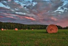 Balas de heno en un prado contra el cielo hermoso con las nubes en puesta del sol Foto de archivo