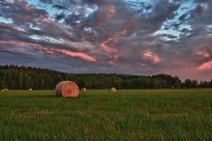 Balas de heno en un prado contra el cielo hermoso con las nubes en puesta del sol Imágenes de archivo libres de regalías