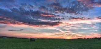 Balas de heno en un prado contra el cielo hermoso con las nubes en puesta del sol Foto de archivo libre de regalías