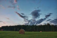 Balas de heno en un prado contra el cielo hermoso con las nubes en puesta del sol Fotos de archivo libres de regalías