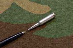 Balas de plata del rifle contra la pluma - un concepto de la libertad de prensa imagen de archivo libre de regalías