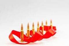 Balas del rifle Manga de cobre amarillo Con una cinta roja en un backg blanco Fotografía de archivo