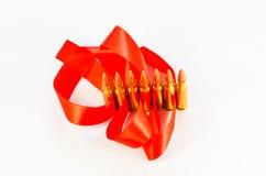 Balas del rifle Manga de cobre amarillo Con una cinta roja en un backg blanco Imagen de archivo libre de regalías