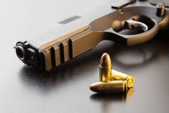 Balas y negro pistola semiautomática de 9 milímetros en superficie negra imagen de archivo libre de regalías