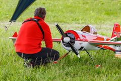 Balashikha, Moscow region, Russia - May 25, 2019: Pilot near big scale RC model of aerobatic aircraft YAK-55 with gasoline engine. On a green lawn. Aviation royalty free stock photography