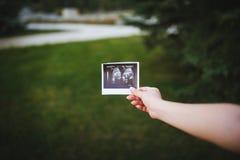 Balayage d'ultrason de bébé dans des mains sur le bakcground vert Images stock