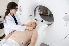 Balayage de docteur Preparing Patient For CT dans l'hôpital Image stock