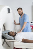 Balayage de docteur About To Start CT sur le patient masculin Photographie stock libre de droits