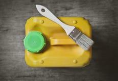 Balayez et jaunissez la peinture de boîte métallique de peinture sur un plan rapproché en bois de table Photo libre de droits