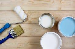Balayez le rouleau de peinture et la peinture sur les conseils en bois Photos stock