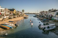 Balboa Island, Newport Beach, CA. Balboa Island houses, small boats, speed boats and people in the water stock images