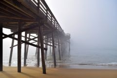Pier disappears into the Fog. Balboa Pier disappears into the fog during the morning sunrise at Newport Beach California royalty free stock photography