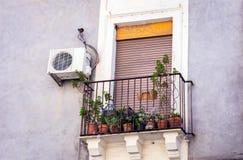 Balcão com vasos de flores e plantas da casa em uma construção histórica em Catania, arquitetura tradicional de Sicília, Itália imagens de stock