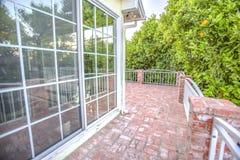 Balcão exterior no meio das árvores alaranjadas e das janelas de vidro imagens de stock royalty free
