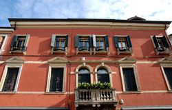 Balcão florescido vermelho do palácio com dez janelas e as duas portas de vidro em Monselice no Vêneto (Itália) Imagem de Stock Royalty Free