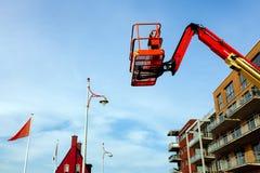Balcão novo velho da casa vermelha da grua da construção do elevador do crescimento do fundo do céu azul em cima foto de stock royalty free