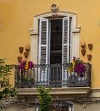 Balcón adornado con las flores y los potes con una puerta en Valencia, España imagen de archivo