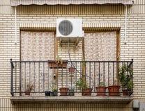 Balcón con las flores en potes, cortinas y una máquina de la CA Fotos de archivo