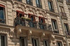 Balcón con las flores en una fachada del edificio y día soleado en el distrito de Montmartre en París Imagenes de archivo