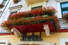 Balcón con las flores rojas hermosas y un hotel del letrero sobre t imagenes de archivo