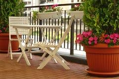 Balcón con muebles de madera y el pequeño jardín decorativo fotografía de archivo libre de regalías